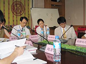 写真5 研究発表:竹田健二(右)、 司会:湯浅邦弘(左)、通訳:崔英(中央)